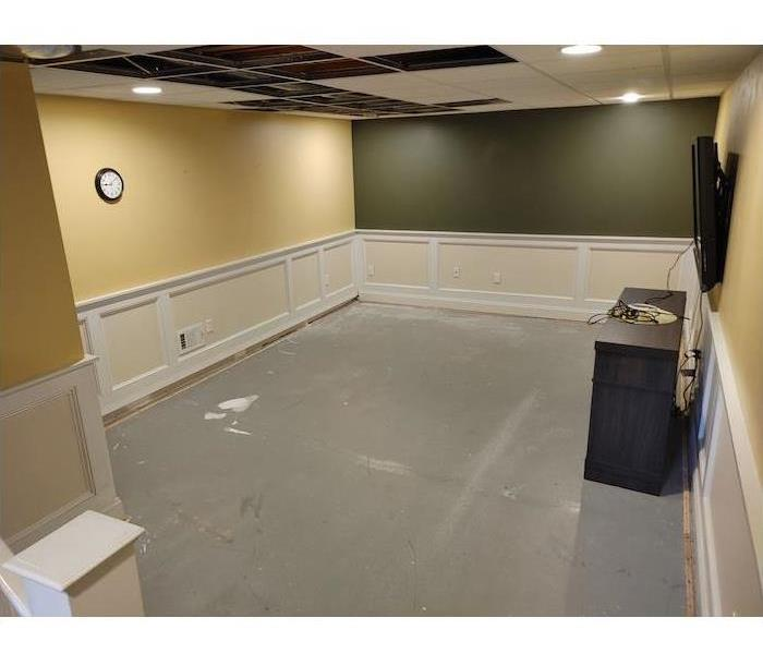 Basement with missing ceiling tiles and concrete floor