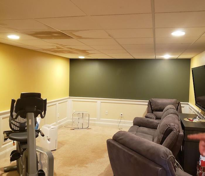 Basement with water stains on the ceiling and a television and recliners