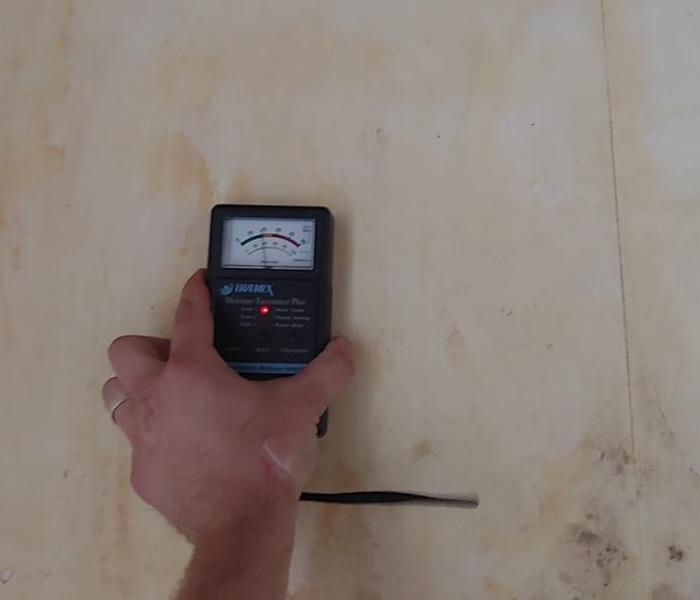 SERVPRO using a moisture meter on a wall